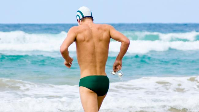 "Man in speedos or ""budgie smugglers"" running on the surf"