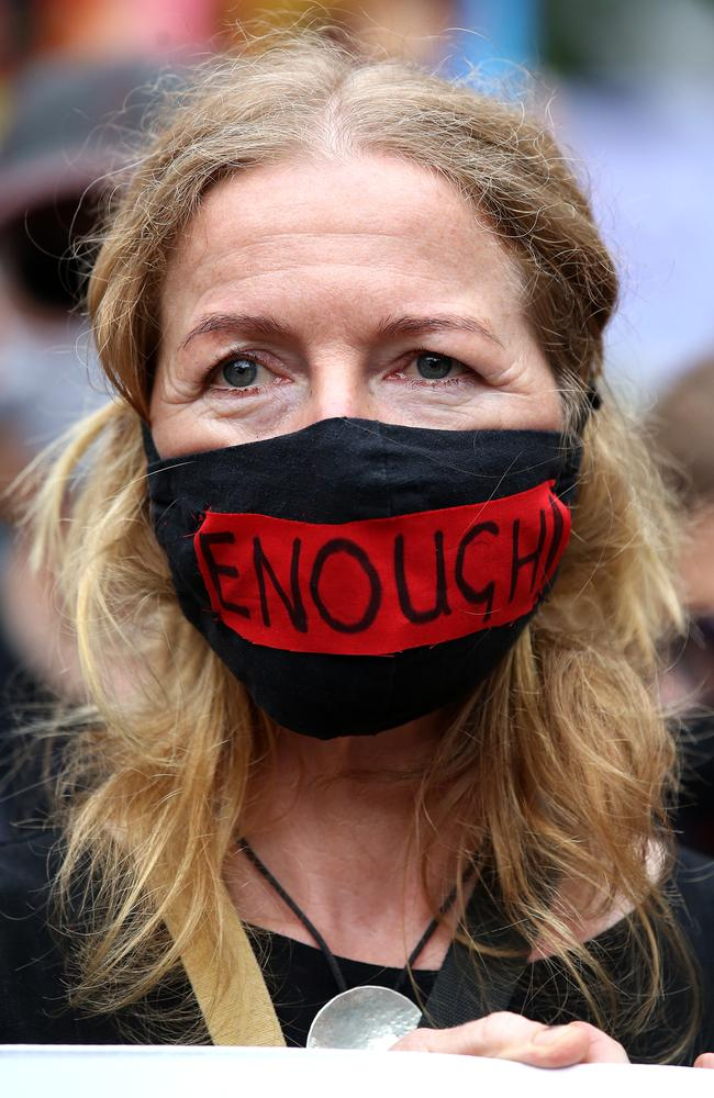 """A protester in Brisbane wears a face mask with the word """"enough"""". Picture: Jono Searle/Getty Images"""