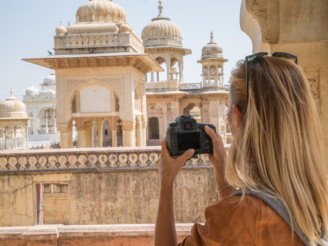 Tourist photographing ancient temple using camera, Jaipur, Rajasthan, India. People travel Asia concept