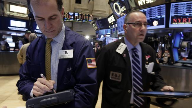 Trader Mark Puetzer, left, works on the floor of the New York Stock Exchange, Friday, Jan. 30, 2015. U.S. financial markets veered lower in morning trading Friday as investors sifted through corporate earnings and economic news. (AP Photo/Richard Drew)