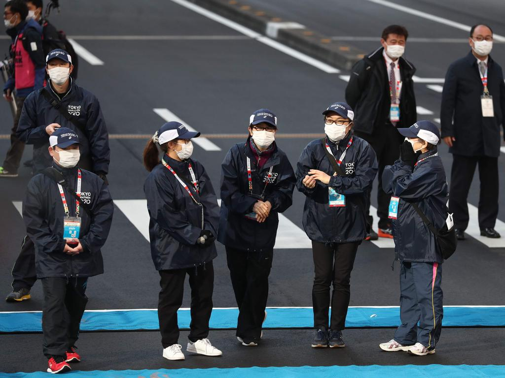 Officials in face masks stand at the starting point. (Photo by ATHIT PERAWONGMETHA / POOL / AFP)