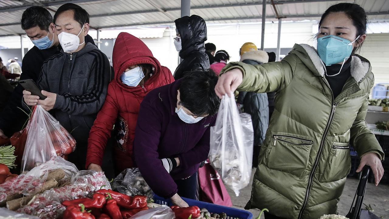 Wuhan residents wear masks to buy vegetables in the market. Picture: Getty Images