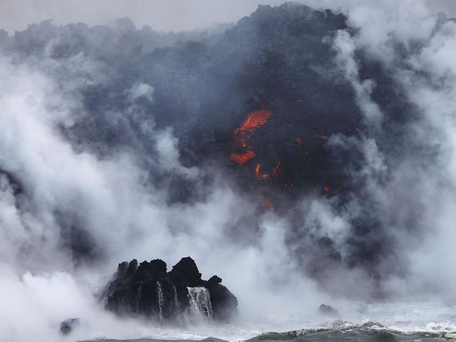 A steam plume rises as lava enters the Pacific Ocean, after flowing to the water from a Kilauea volcano fissure, on Hawaii's Big Island on May 20. Picture: AFP