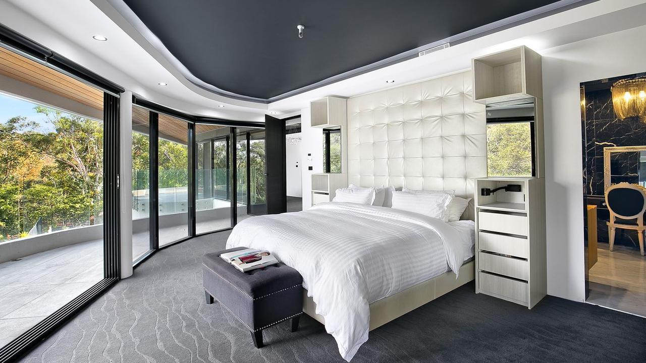 The bedroom has floor to roof windows.