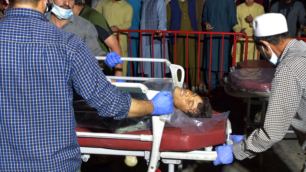 Medical staff bring an injured man to hospital after the bombing. Picture: Wakil Kohasar/AFP )