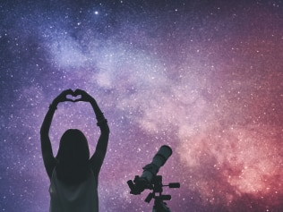 Girl making a heart-shape for the stars with telescope beside her. Milky Way stars are my astronomy work, no elements of NASA or other third party.