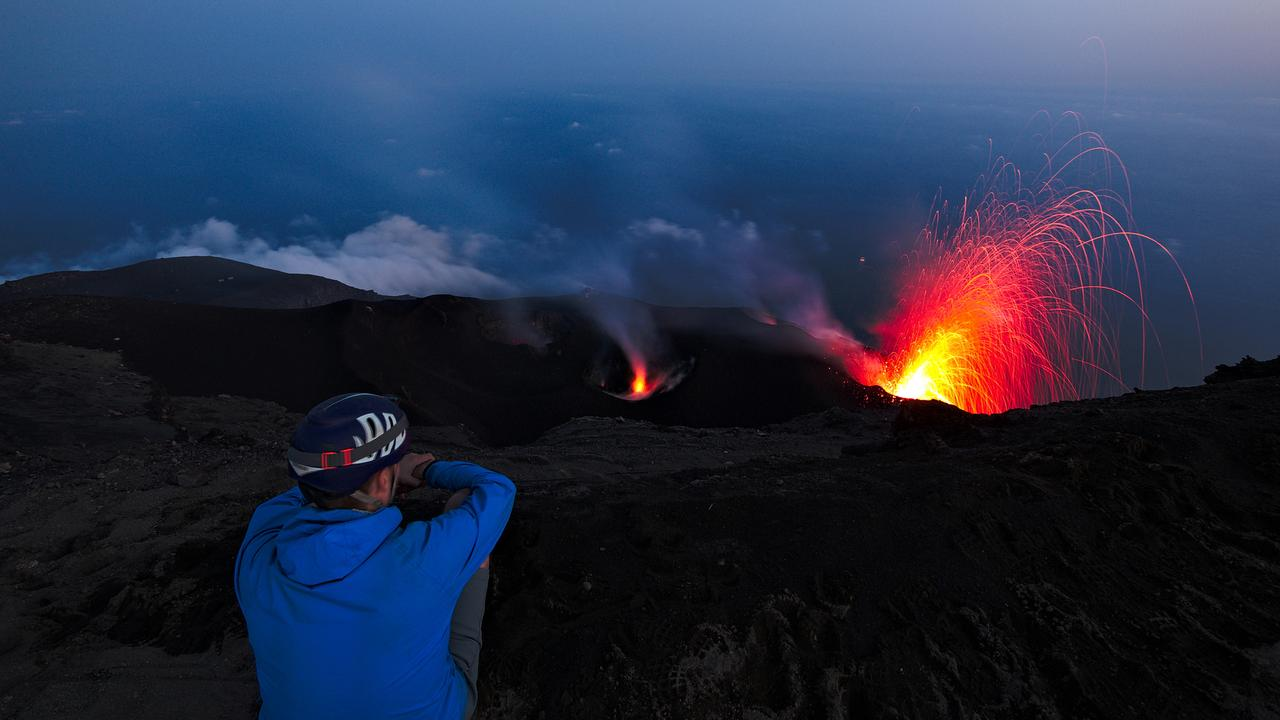A tourist watching the volcano eruption at night at Stromboli in Italy.
