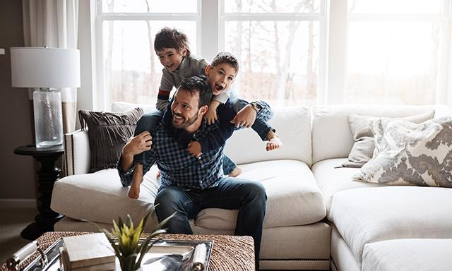 Two boys wrestling at home with dad