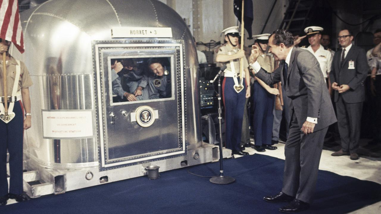 "Then US President Richard Nixon gives an ""OK"" sign as he greets Apollo 11 astronauts Neil Armstrong, Michael Collins and Buzz Aldrin in a quarantine van on July 24 aboard the USS Hornet after splashdown and recovery in the Pacific Ocean. Picture: AP"