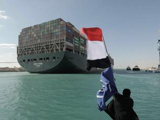 A picture released by Egypt's Suez Canal Authority on March 29, 2021, shows a man waving the Egyptian flag after Panama-flagged MV 'Ever Given' container ship was fully dislodged from the banks of the Suez. - The ship was refloated and the Suez Canal reopened, sparking relief almost a week after the huge container ship got stuck and blocked a major artery for global trade. Salvage crews have been working around the clock ever since the accident which has been blamed on high winds and poor visibility during a sandstorm. (Photo by - / SUEZ CANAL AUTHORITY / AFP)