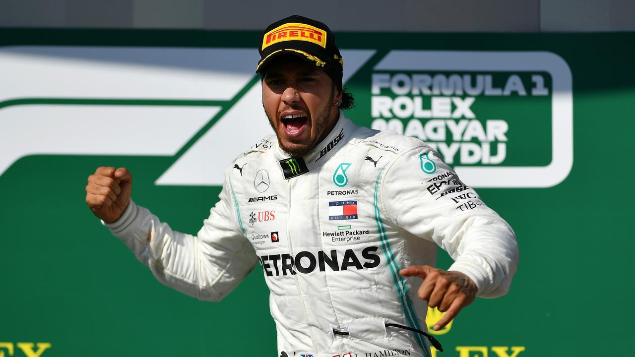 Race winner Hamilton celebrates on the podium at the Hungaroring.