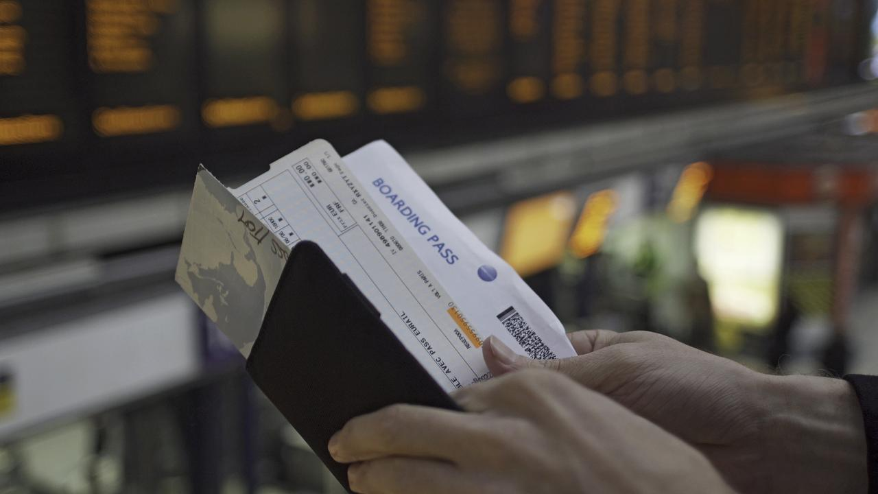 A pair of man's hands checks his travel documents and the time on his wristwatch. In the background is a large, out of focus, electronic departures board.