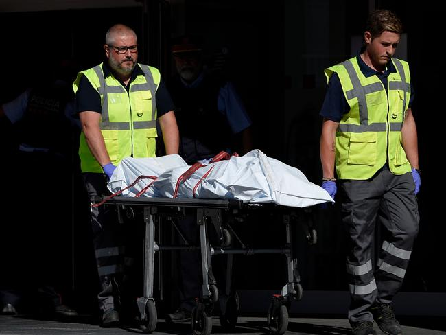 The body of a man who tried to attack a police station is carried out of the premises. Picture: AFP