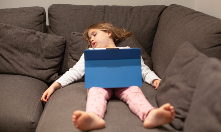 five years old blonde child in pajamas sleeping lying on the coach, with digital tablet on her legs