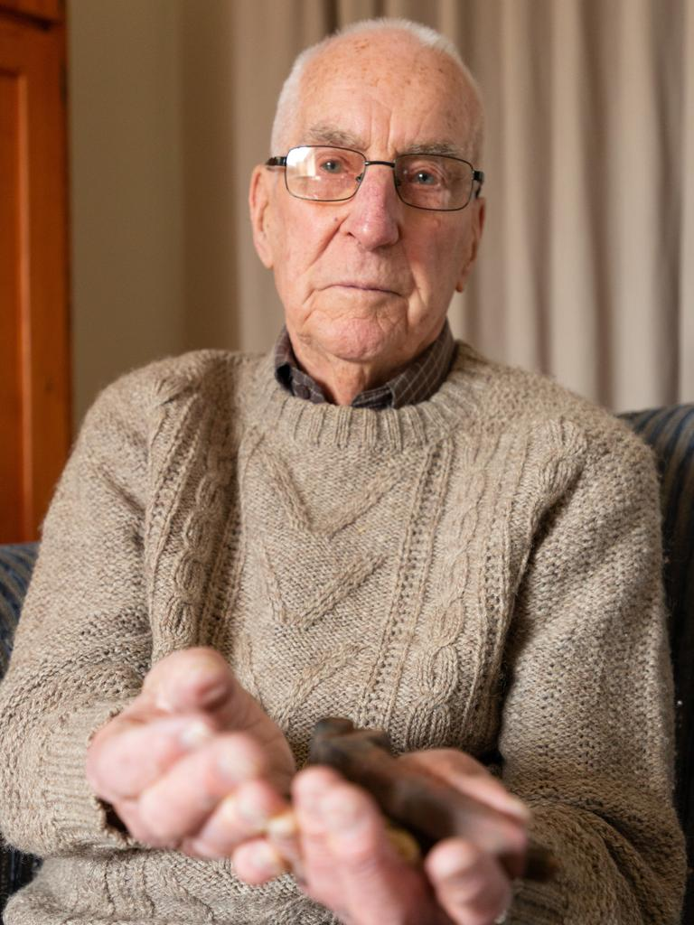 Death Railway veteran James Kerr watches the Anzac360 VR film of Hellfire Pass, at his home in Melbourne with Justin Lees of News360. Pictured with nails and wood from the railway that he keeps as a reminder of his survival. Picture: Maxim Drygin.