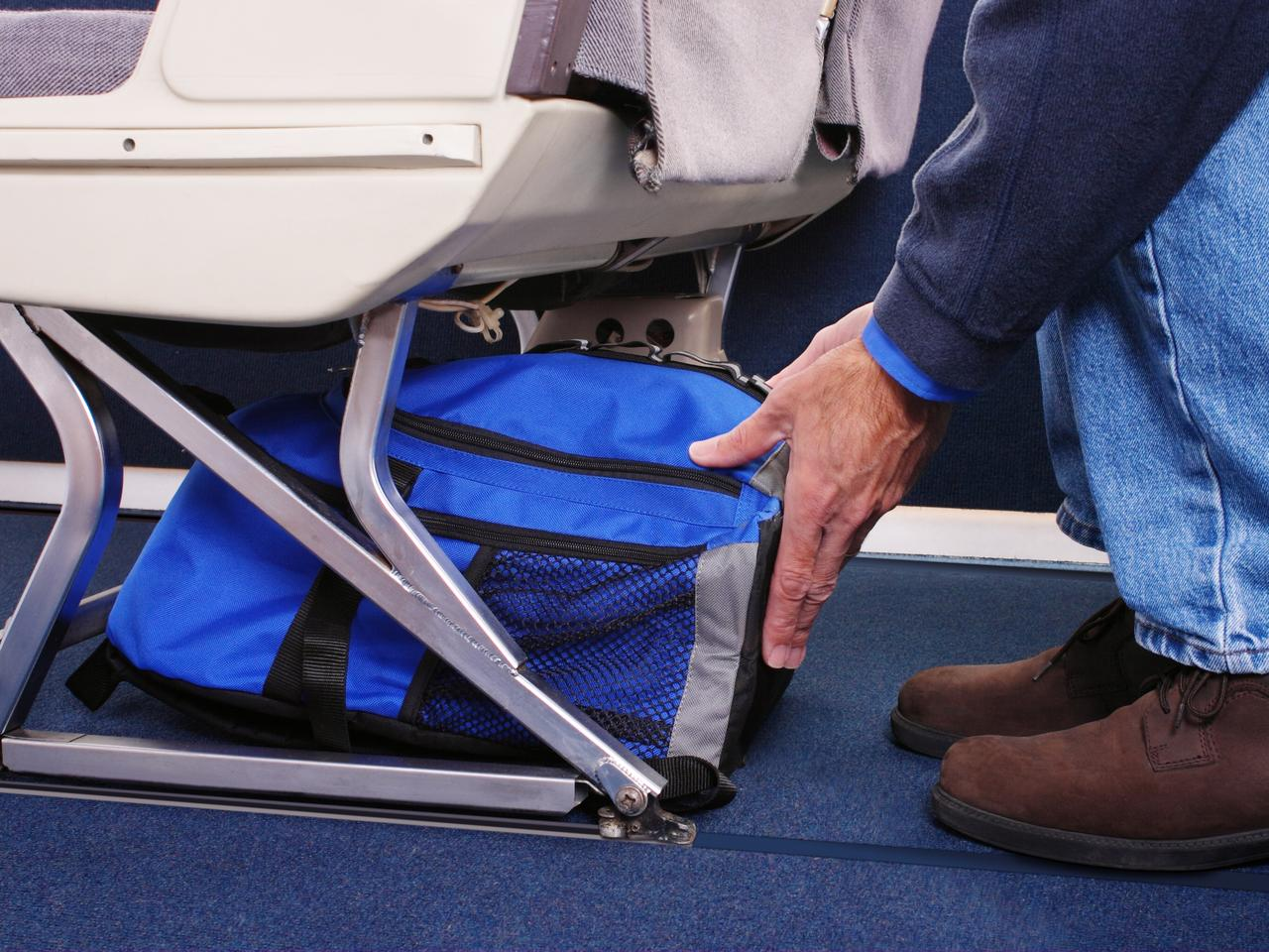 Airplane passenger stowing his carry-on luggage under the seat in front of him.