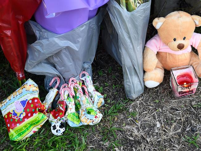 Flowers and toys lie against a fence across the road from the scene of the child massacre.