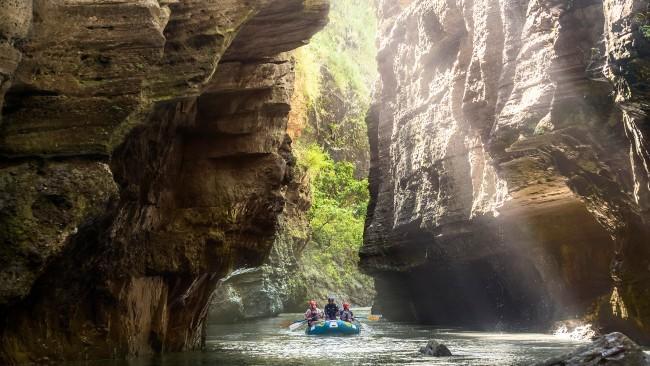 Group rafting through canyon river.
