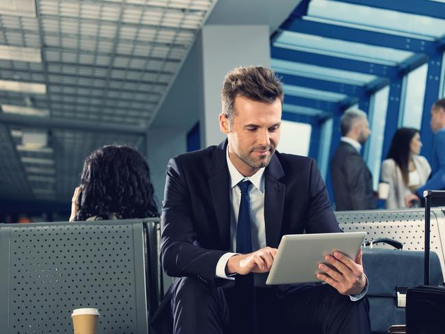 Businessman waiting for a flight at the airport lounge, using a digital tablet with group of people standing in the background. Photo: istock