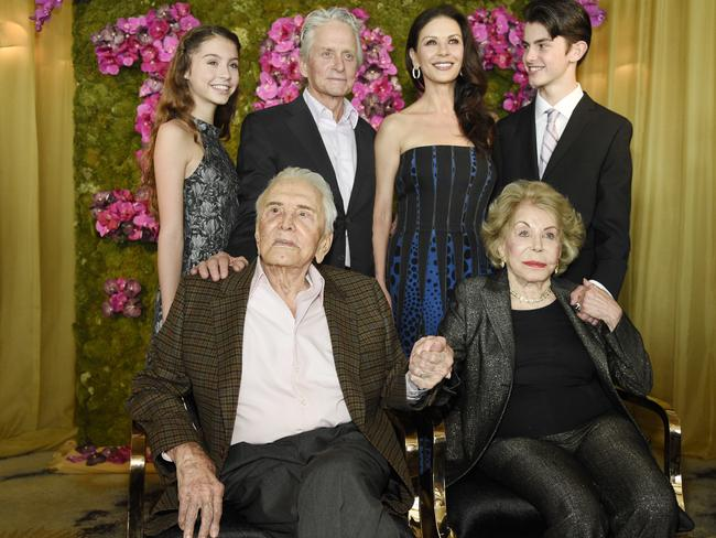 Actor Kirk Douglas, holds hands with his wife Anne Douglas, as they pose with family members, their son Michael, his wife Catherine Zeta-Jones, and their children, Carys Zeta Jones and son Dylan at Kirk's 100th birthday party. Picture: Chris Pizzello/Invision/AP