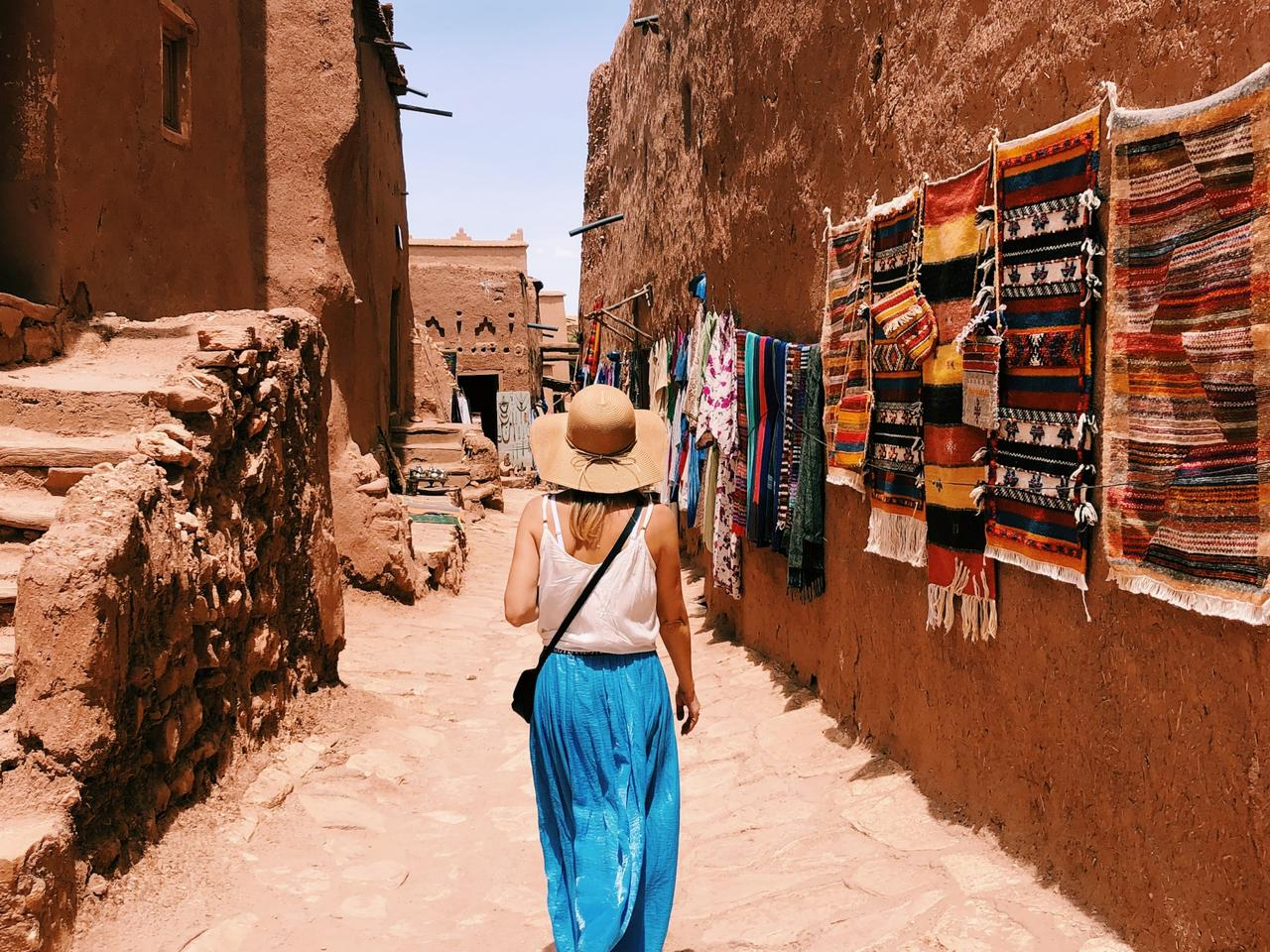 Young woman walking along narrow streets of Ait Ben Haddou village in Morocco