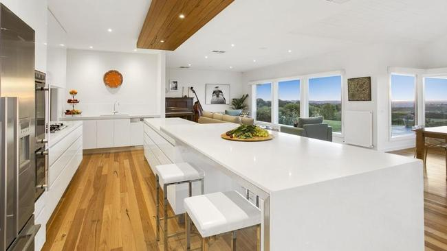 The kitchen has a long island bench and built-in dining table.