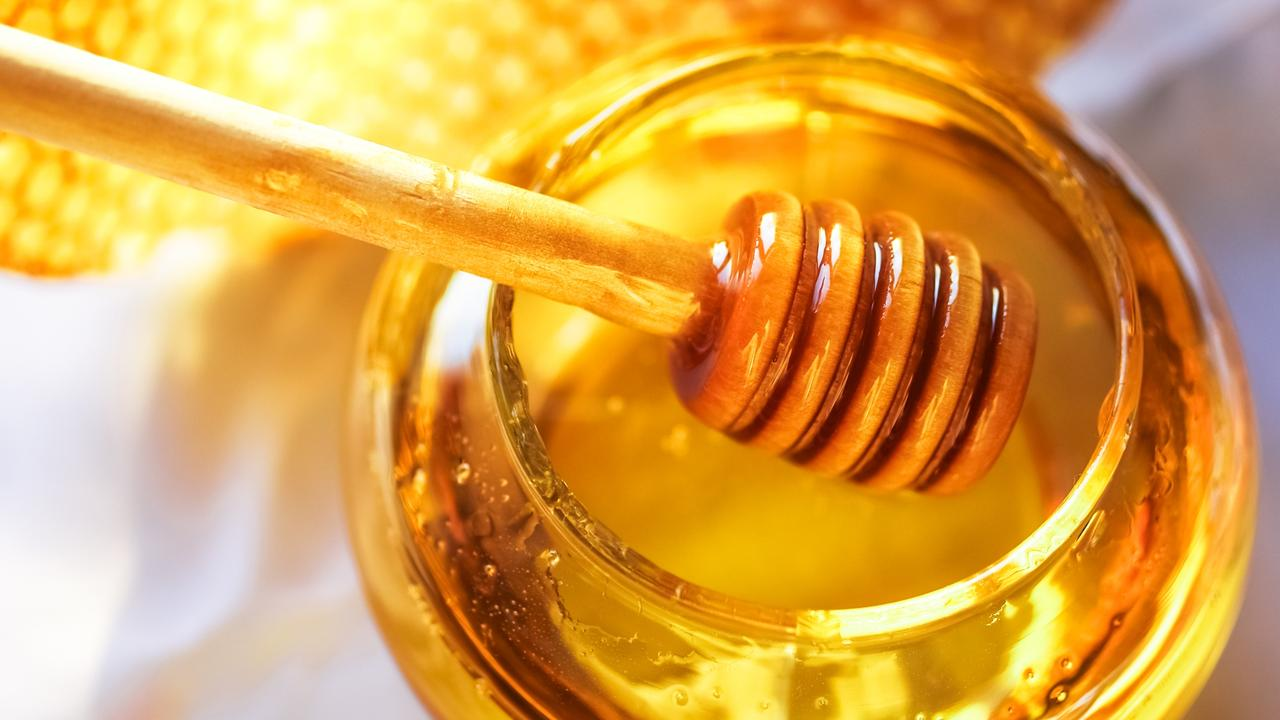 Honey in a glass jar next to honeycombs