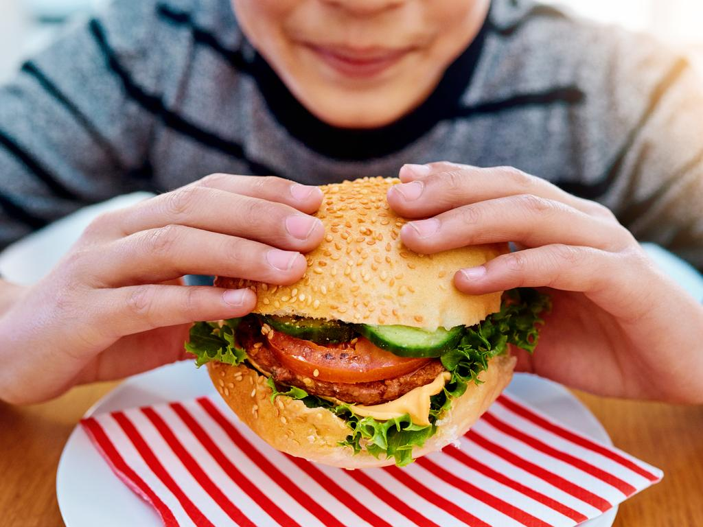 Shot of an unrecognizable young boy eating a delicious burger while sitting at his table at home