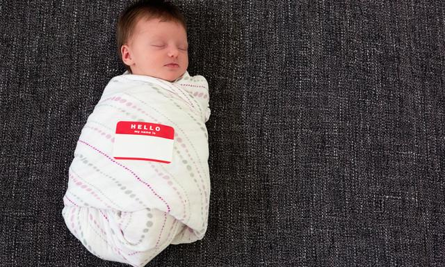 """Sleeping swaddled infant with a """"Hello my name is"""" sticker"""
