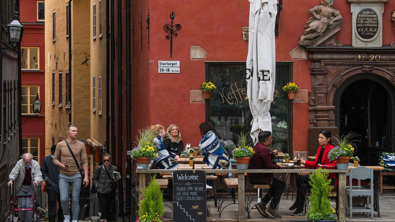 People sit in a restaurant in Stockholm in May when, in much of the rest of the world, people were huddled indoors. Picture: Jonathan NACKSTRAND / AFP