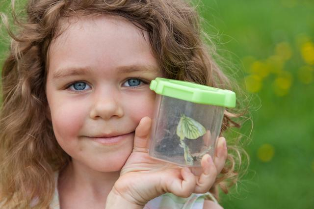 The lovely girl of 4 years old holds the container with the caug