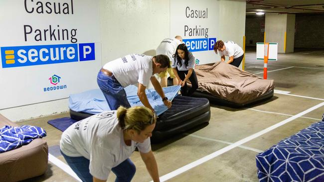 Beddown volunteers make up beds in the recent Brisbane carpark trial. Picture: supplied