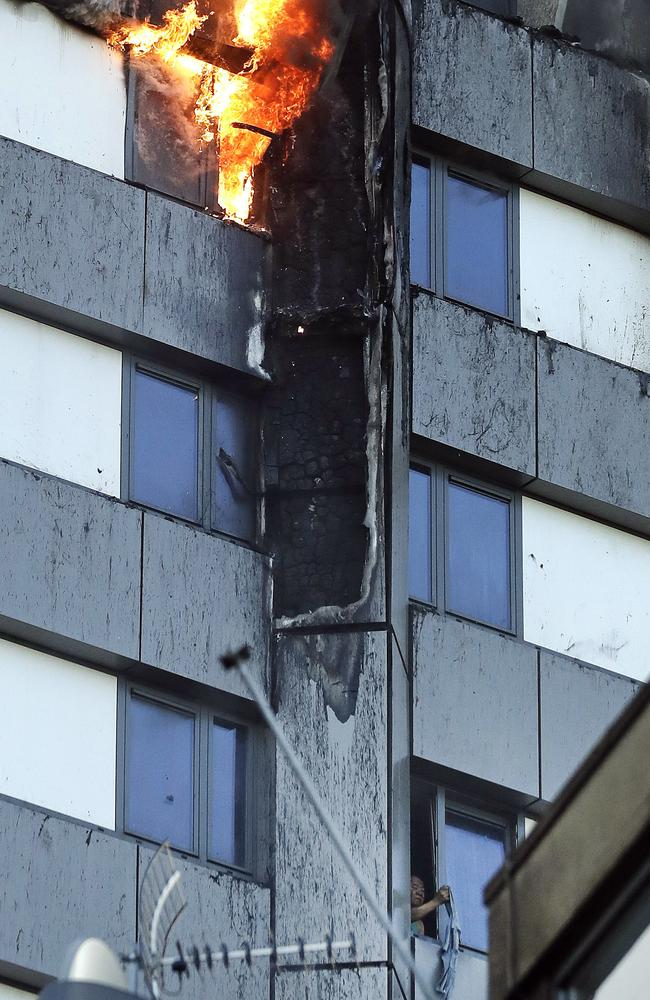 A person, bottom right, peers out of a window from the fire. Picture: AP