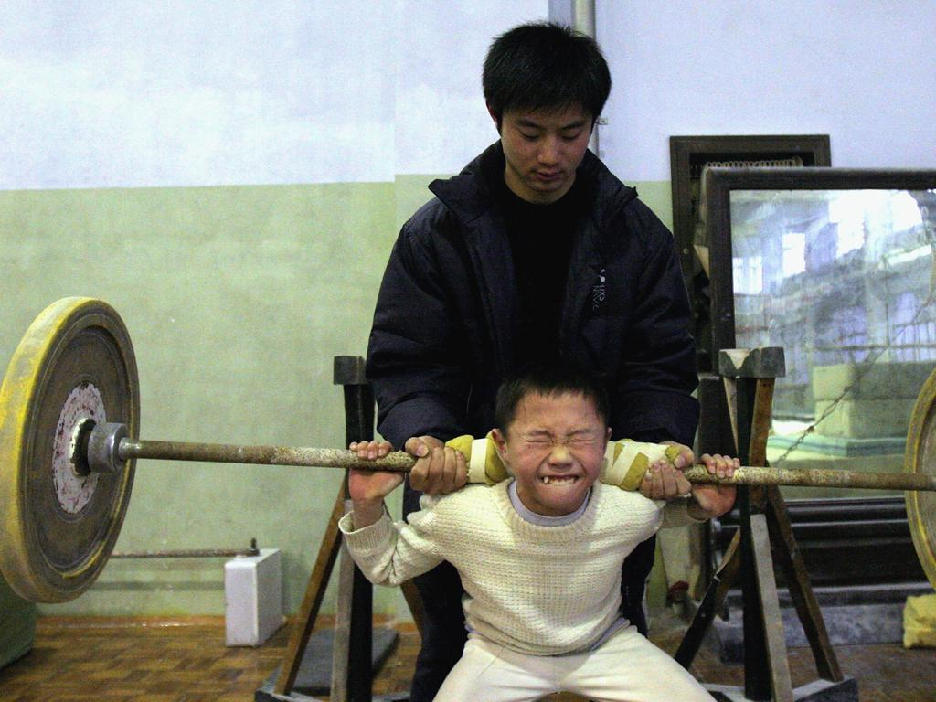 A young boy tries to lift a weight with the help of his coach at Chengdu Children's Gymnastics School in 2005 in Chengdu, China. Picture: Getty Images