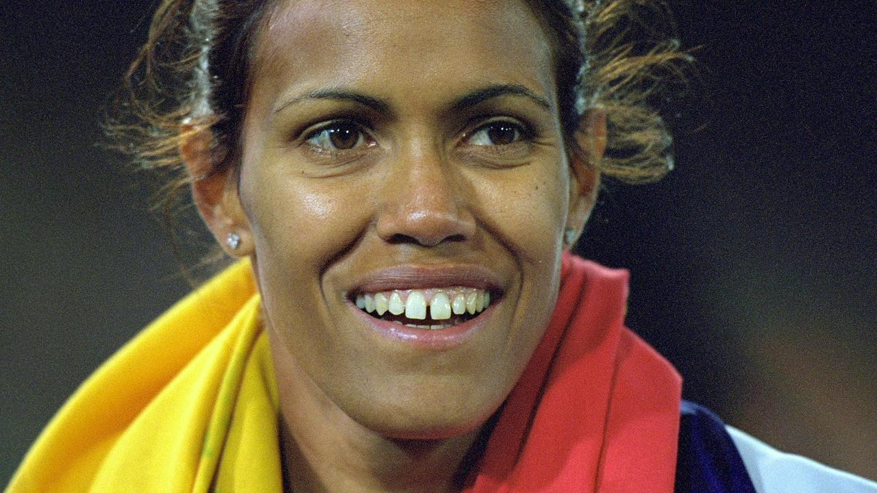 Cathy Freeman celebrates her Olympic gold with the Indigenous and Australian flags.
