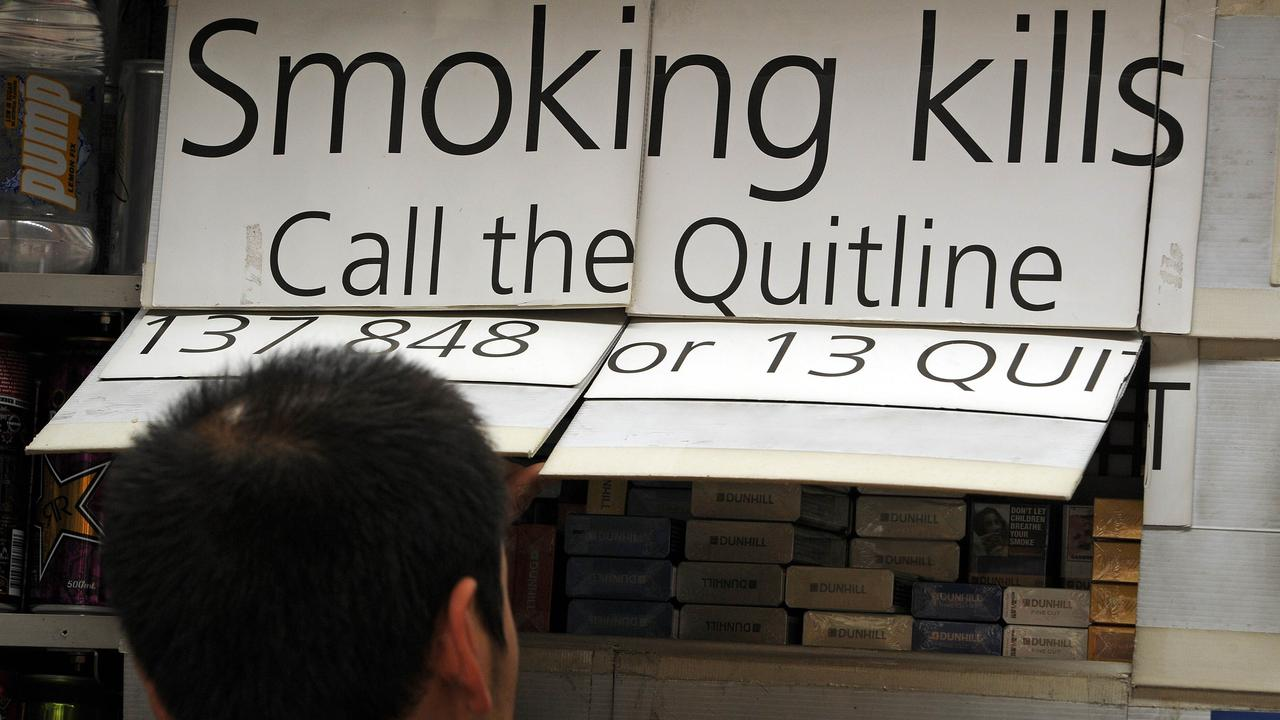 "A kiosk worker (below) looks at cigarette packets which are kept covered up by law in central Sydney on August 15, 2012. Global tobacco firms lost a ""watershed"" court challenge to Australia's plain packaging laws for cigarettes on August 15 in a closely-watched case health advocates said will have a worldwide impact. The High Court of Australia ruled the measures, forcing cigarettes and tobacco products to be sold in drab, uniform packaging with graphic health warnings from December 1 this year, did not breach the country's constitution.  AFP PHOTO / Greg WOOD"