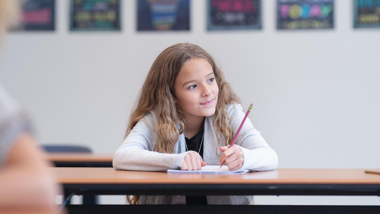 Elementary age girl working on writing assignment in school