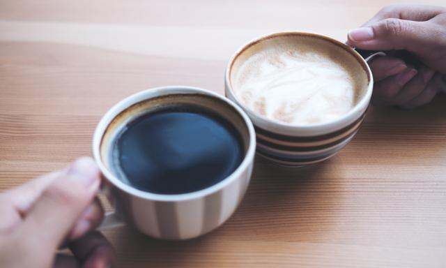 Top view image of man and woman's hands holding coffee cups with wooden table background