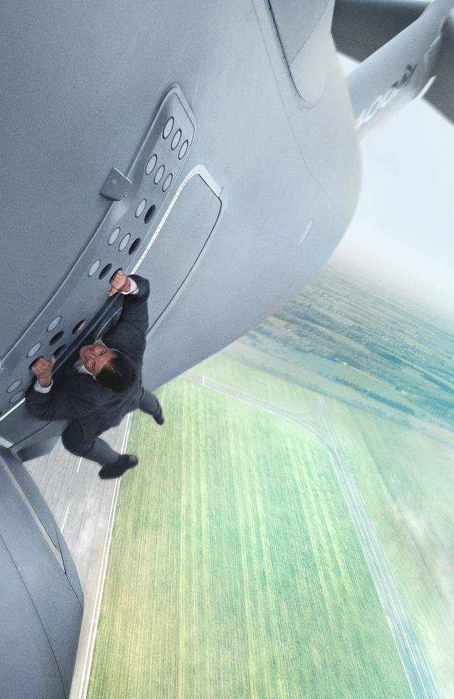 Tom Cruise hanging off the side of a plane in Mission: Impossible Rogue Nation.