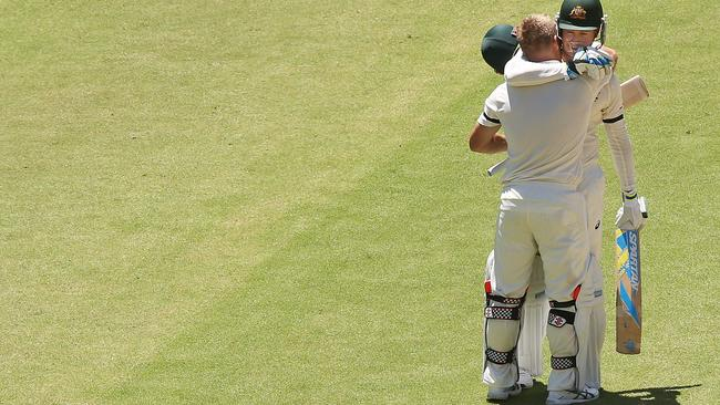 Poignant: David Warner of Australia celebrates making his century with Michael Clarke during day one of the First Test match between Australia and India. Picture: Michael Dodge/Getty Images