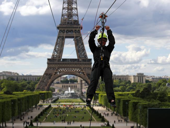 A participant rides a zipline tied from the second floor of the Eiffel Tower, 115 metres above the Champ de Mars gardens along an 800-meters long cable, as part of a free event in Paris, France, Tuesday, May 28, 2019. (AP Photo/Francois Mori)
