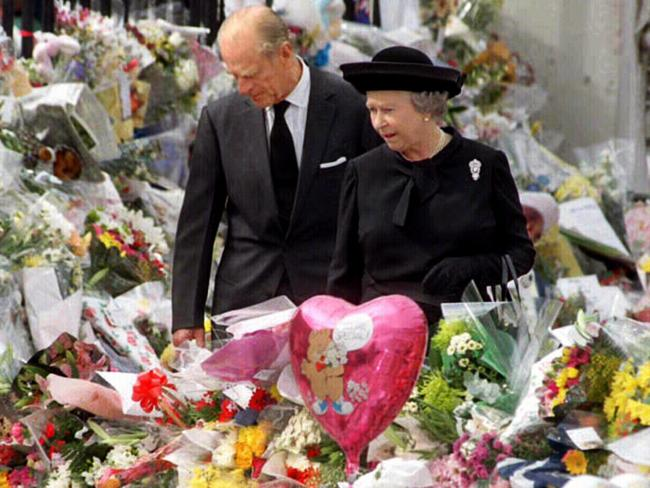 The Duke of Edinburgh, Prince Philip and Queen Elizabeth II, walking through a sea of floral tributes outside Buckingham Palace after Diana's death. Picture: AFP