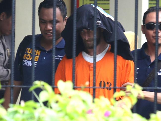David Taylor escorted by police officers for interrogation at Denpasar Police Station. Picture: Lukman S. Bintoro
