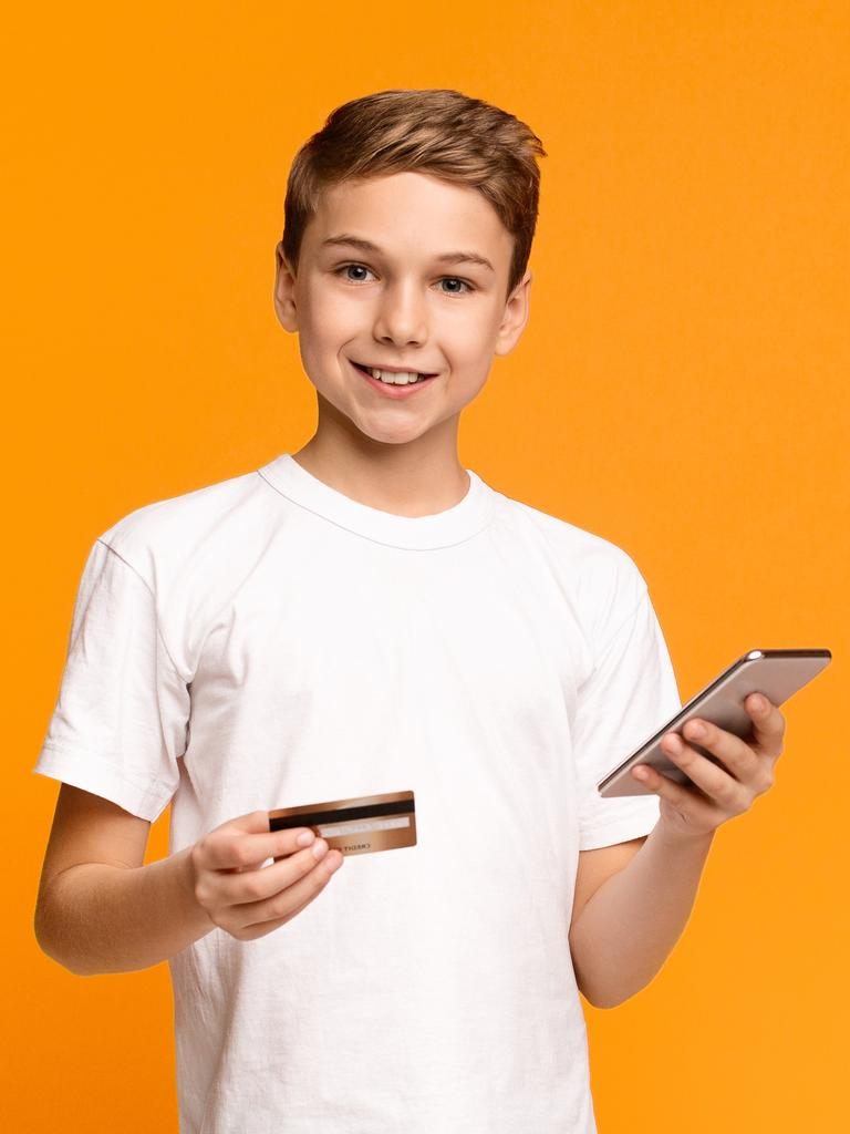 Cute teenager using mobile application and credit card