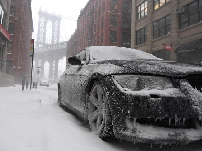 A car covered in ice is parked in front of the Manhattan Bridge in Brooklyn, New York. Picture: AFP/Angela Weiss