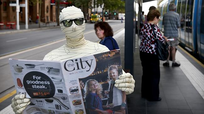 Adam Murphy, who plays Storey in Horrible Histories, gets a copy of News Corp's news publication The City. Picture: Mike Burton