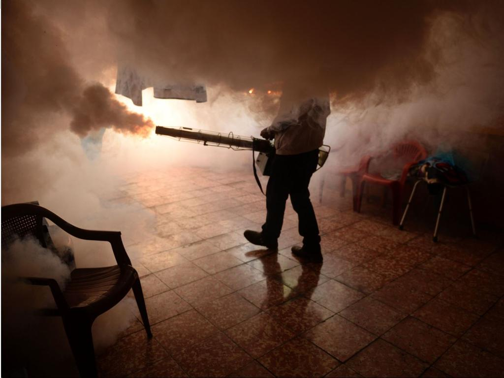 A worker fumigates a public facility to contain the spread of the Zika virus in South America.
