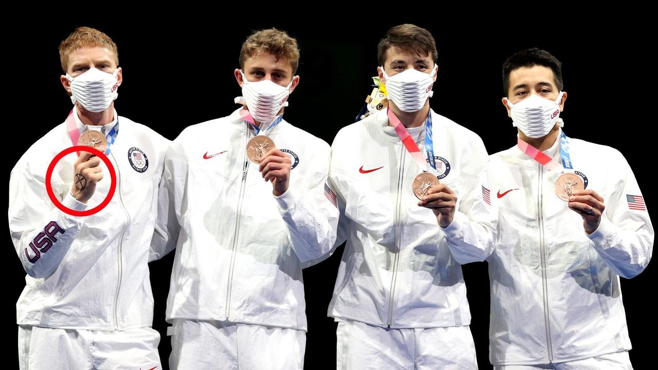 """Race Imboden displayed an """"X"""" on his hand in a """"symbol of solidarity"""" for the medal ceremony. Picture: Elsa/Getty Images"""