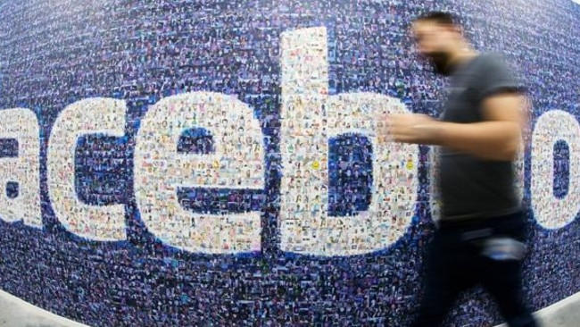 This picture taken with a fisheye lens shows a man walks past a big logo created from pictures of Facebook users worldwide in the company's Data Center, its first outside the US on November 7, 2013 in Lulea, in Swedish Lapland. The company began construction on the facility in October 2011 and went live on June 12, 2013 and are 100% run on hydro power. AFP PHOTO/JONATHAN NACKSTRAND