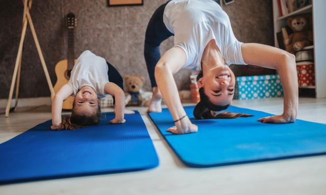 Mother and daughter working out together doing exercise at home